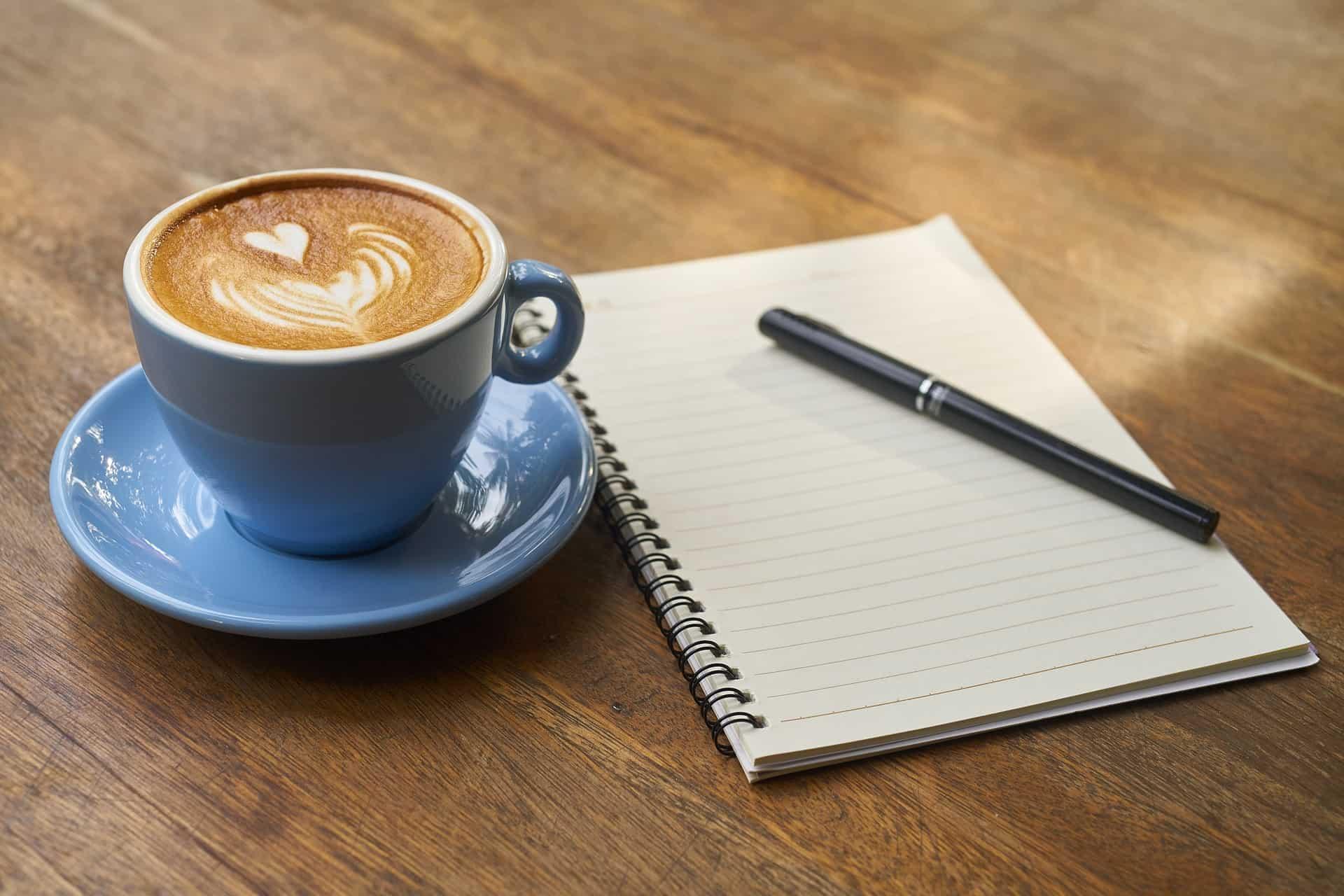 Eine Tasse Kaffee und ein Notizblock mit Stift