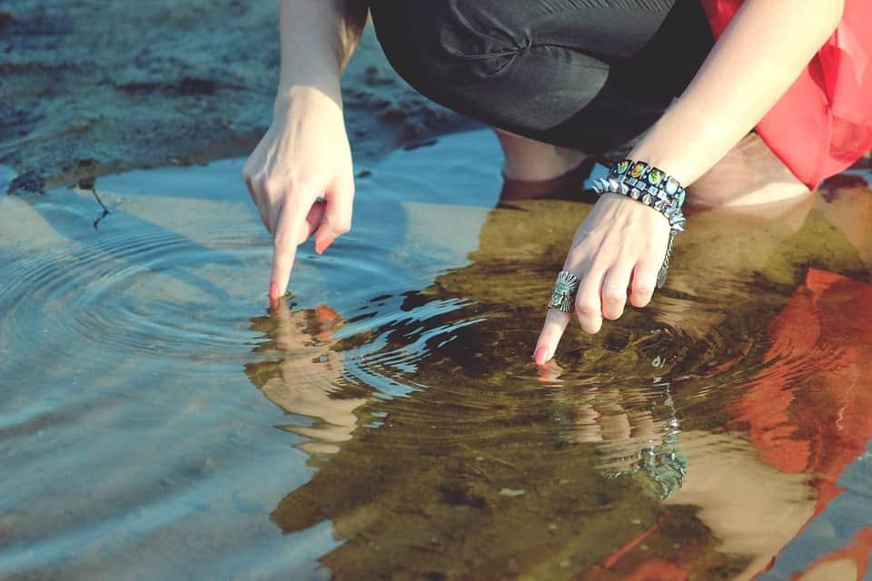 Finger die im Wasser Ringe erzeugen
